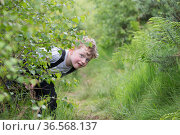 Boy hiding during forest kindergarten session. Aberdeen, Aberdeenshire, Scotland, UK. Editorial use only. Редакционное фото, фотограф SCOTLAND: The Big Picture / Nature Picture Library / Фотобанк Лори