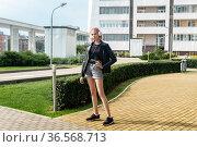 Teen girl listening to music walking around the city. Стоковое фото, фотограф Евгений Харитонов / Фотобанк Лори