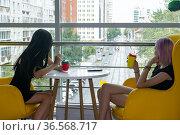 Two teenage girls drinking a cocktail in the cafeteria. Стоковое фото, фотограф Евгений Харитонов / Фотобанк Лори
