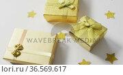 Video of gold christmas presents and stars on white background. Стоковое видео, агентство Wavebreak Media / Фотобанк Лори