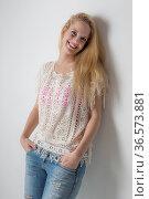 Junge Frau in Jeans und Häkelshirt leht an einer Wand. Стоковое фото, фотограф Zoonar.com/Hans Eder / easy Fotostock / Фотобанк Лори
