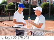 grandfather and grandson talking on court playing tennis. Стоковое фото, фотограф Татьяна Яцевич / Фотобанк Лори