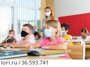 Small school girl in face mask sitting at desk in classroom. Стоковое фото, фотограф Яков Филимонов / Фотобанк Лори