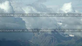 Time lapse video of clouds running over snow mountain peaks in Altai