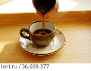 Hot turkish coffee pouring from cezve into ceramic espresso cup on saucer. Bamboo wood tray. Стоковое фото, фотограф Кристина Сорокина / Фотобанк Лори