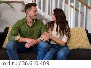 Happy caucasian couple sitting on sofa and looking at each other. Стоковое фото, агентство Wavebreak Media / Фотобанк Лори