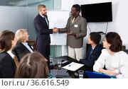 Two businessman shaking hands in meeting room, confirming successful international partnership. Стоковое фото, фотограф Яков Филимонов / Фотобанк Лори