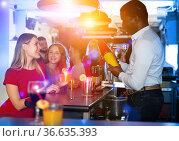 Man bartender shaking cocktail mixer for women in nightclub. Стоковое фото, фотограф Яков Филимонов / Фотобанк Лори