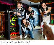 Modern young people with laser pistols playing laser tag on dark labyrinth. Стоковое фото, фотограф Яков Филимонов / Фотобанк Лори