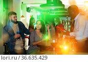 Male bartender shaking cocktail mixer for couple at nightclub. Стоковое фото, фотограф Яков Филимонов / Фотобанк Лори