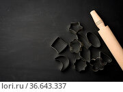 Metal cookie cutters and wooden rolling pin on a black background... Стоковое фото, фотограф Zoonar.com/Danko Natalya / easy Fotostock / Фотобанк Лори