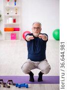 Old man doing sport exercises indoors. Стоковое фото, фотограф Elnur / Фотобанк Лори