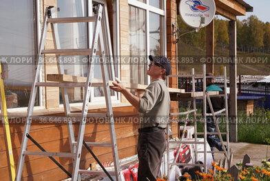 Рабочий устанавливает строительные леса у стены деревянного дома в солнечный осенний день