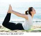 Female 20-30 years old is practicing stretching in white T-shirt. Стоковое фото, фотограф Яков Филимонов / Фотобанк Лори