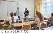 Portrait of diligent teenager schoolboy answering at board to teachers question in front of group of students in classroom. Стоковое видео, видеограф Яков Филимонов / Фотобанк Лори