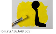 Silhouette of hand holding a ball against yellow paint stain and brush on white background. Стоковое фото, агентство Wavebreak Media / Фотобанк Лори