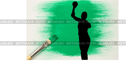 Silhouette of female handball player against green paint stain and paint brush on white background