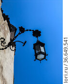 Ancient street light hanging on the external wall of the chapel dedicated... Стоковое фото, фотограф Angelo Calvino / age Fotostock / Фотобанк Лори