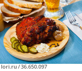 Oven baked pork knuckle with boiled onions and pickled cucumbers. Стоковое фото, фотограф Яков Филимонов / Фотобанк Лори