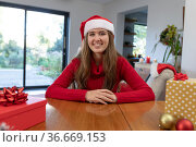 Happy caucasian woman wearing santa hat having video call at christmas time. Стоковое фото, агентство Wavebreak Media / Фотобанк Лори