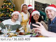 Group of happy diverse female and male friends in santa hats , celebrating christmas, taking selfie. Стоковое фото, агентство Wavebreak Media / Фотобанк Лори