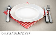 Serving plate, spoon, fork, knife and napkin standing on tablecloth... Стоковое фото, фотограф Zoonar.com/Cigdem Simsek / easy Fotostock / Фотобанк Лори