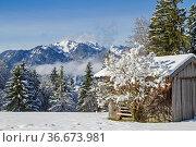 Winter im Isarwinkel - Heuhütte vor den schneebedeckten Bergen der... Стоковое фото, фотограф Zoonar.com/Eder Christa / easy Fotostock / Фотобанк Лори