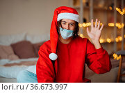 Caucasian guy in face mask and Santa Claus hat posing and looking... Стоковое фото, фотограф Zoonar.com/Oleksii Hrecheniuk / easy Fotostock / Фотобанк Лори
