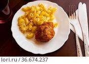Dish of Russian cuisine is a meat cutlet with macaroni. Стоковое фото, фотограф Яков Филимонов / Фотобанк Лори