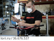 Workers at work in the new headquarters of Fantic Motor bicycle and... Редакционное фото, фотограф Mirco Toniolo / AGF/Mirco Toniolo / AGF / age Fotostock / Фотобанк Лори