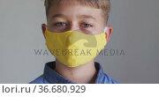 Portrait close up of a caucasian boy putting on a yellow face mask. Стоковое видео, агентство Wavebreak Media / Фотобанк Лори