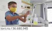 Caucasian boy wearing yellow facemask standing at kitchen sink washing hands under running tap. Стоковое видео, агентство Wavebreak Media / Фотобанк Лори
