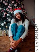Cute african american woman sits near a Christmas tree, posing on... Стоковое фото, фотограф Zoonar.com/Oleksii Hrecheniuk / easy Fotostock / Фотобанк Лори