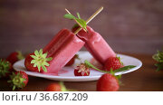 Homemade strawberry ice cream on a stick made from fresh strawberries in a plate. Стоковое видео, видеограф Peredniankina / Фотобанк Лори