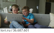 Caucasian boy with his brother sitting in living room and using laptop. Стоковое видео, агентство Wavebreak Media / Фотобанк Лори