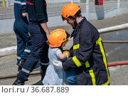Fire uniformed father teaches his daughter Firefighter training. Стоковое фото, фотограф Ирина Аринина / Фотобанк Лори
