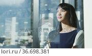 Young woman looking through the window. Стоковое видео, агентство Wavebreak Media / Фотобанк Лори