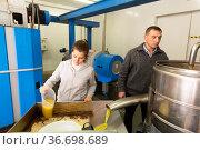 Man and woman inspecting oil decanting. Стоковое фото, фотограф Яков Филимонов / Фотобанк Лори