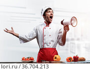 Young chef shouting loudly into megaphone. Emotional caucasian chef... Стоковое фото, фотограф Zoonar.com/Aleksandr Khakimullin / easy Fotostock / Фотобанк Лори
