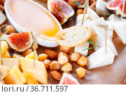 Assortment of cheese on wooden board. a buffet table at a party outdoors... Стоковое фото, фотограф Zoonar.com/Konstantin Malkov / easy Fotostock / Фотобанк Лори