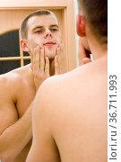 Reflexion of young man in the bathroom's mirror after shave. Стоковое фото, фотограф Zoonar.com/Tomasz Trojanowski / easy Fotostock / Фотобанк Лори