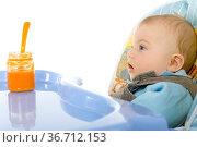 Pretty infant sitting on baby's chair. Looking at orange pulp in jar... Стоковое фото, фотограф Zoonar.com/Tomasz Trojanowski / easy Fotostock / Фотобанк Лори