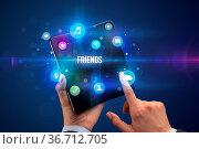 Businessman holding a foldable smartphone with FRIENDS inscription... Стоковое фото, фотограф Zoonar.com/rancz / easy Fotostock / Фотобанк Лори