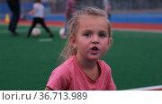 Little girl talks in slowmotion against blurred background. Стоковое видео, видеограф Ekaterina Demidova / Фотобанк Лори
