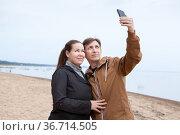 Loving Caucasian couple taking selfie with smartphone while walking on sandy coastline. Стоковое фото, фотограф Кекяляйнен Андрей / Фотобанк Лори