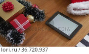 Tablet with copy space and christmas decoration on wooden table. Стоковое видео, агентство Wavebreak Media / Фотобанк Лори