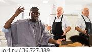 African man unpleasantly surprised by haircut from elderly hairdresser. Стоковое фото, фотограф Яков Филимонов / Фотобанк Лори
