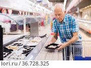 elderly retired senor buying sushi in buffet department of supermarket. Стоковое фото, фотограф Татьяна Яцевич / Фотобанк Лори
