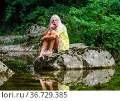 Attractive blonde woman on a Green forest river eating Red apple. Стоковое фото, фотограф Emil Pozar / age Fotostock / Фотобанк Лори
