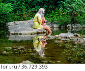 Attractive blonde woman on a Green forest river with flowers in hand. Стоковое фото, фотограф Emil Pozar / age Fotostock / Фотобанк Лори